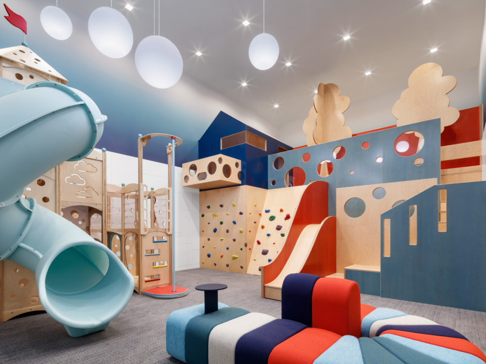 Kids playroom at the Park Loggia in New York. Carpeted room with built in slides and play structures, wall art and a couch.