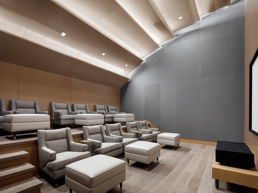 Private screening room at the Park Loggia in New York. Theater room with two rows of seats and large projection screen.