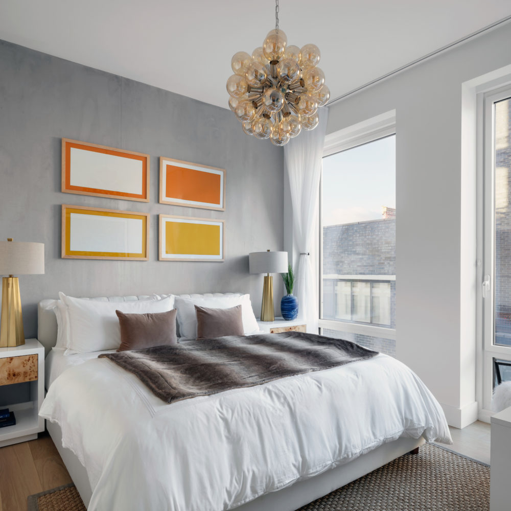 Large bedroom at the Park Loggia luxury condominiums in NYC. Large bed, bedside table and tall windows for natural light.