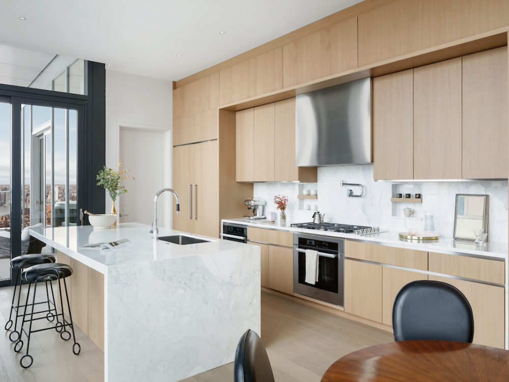 Interior view of kitchen inside 277 Fifth Avenue condominiums in NYC. Includes middle counter and wooden cabinets.