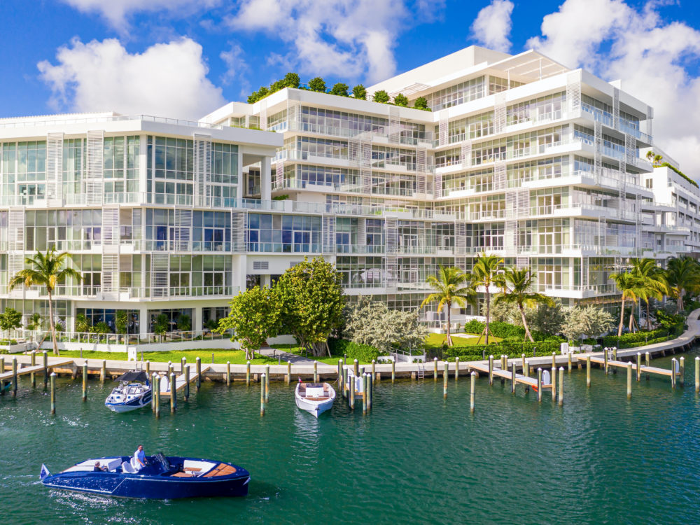 Birds eye view of the Ritz-Carlton Residences in Miami Beach from the water. Boats at the dock curving around the building.