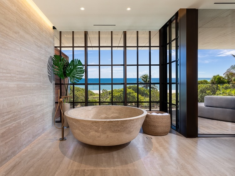 Interior view of Arte Surfside residence bathroom with oceanfront window view. Has smooth flooring and gold bathtub.