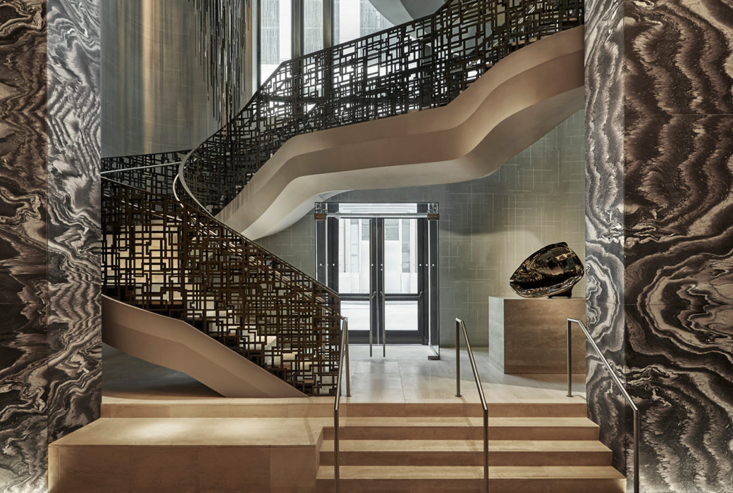 Interior view of 30 Park Place residence lobby in NYC. Includes view of wooden staircase with black rails leading upwards.