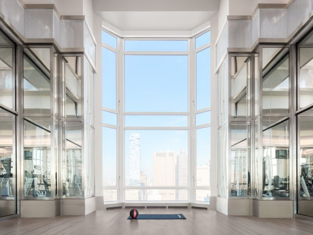 30 Park Place residence fitness center with huge window view of NYC. Includes glass window workout rooms and clear space.