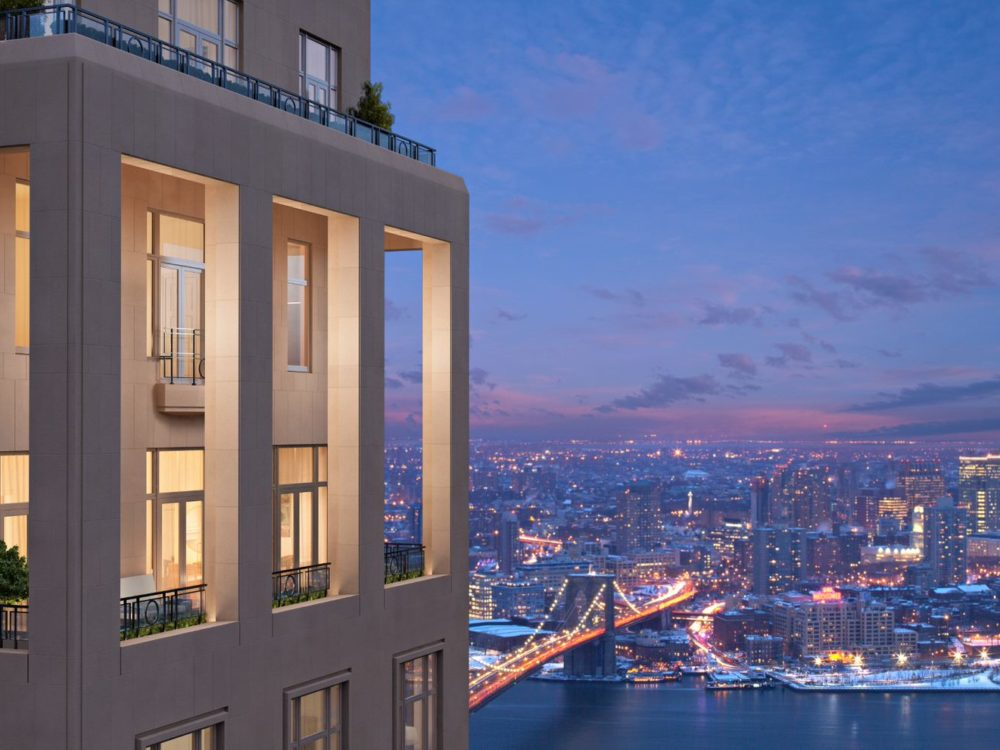 Exterior close up view of balcony at 30 Park Place condominiums with view of New York City and river during the night.
