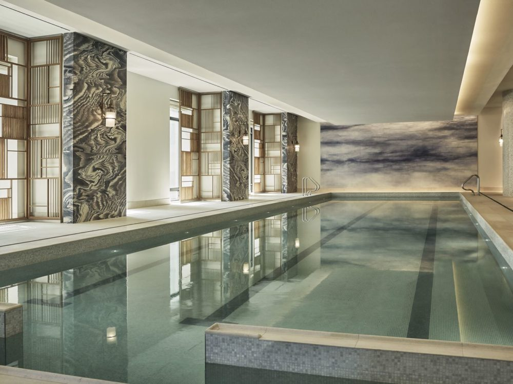 Interior view of 30 Park Place residence indoor lap pool in NYC. Includes white walls and brown tile flooring.