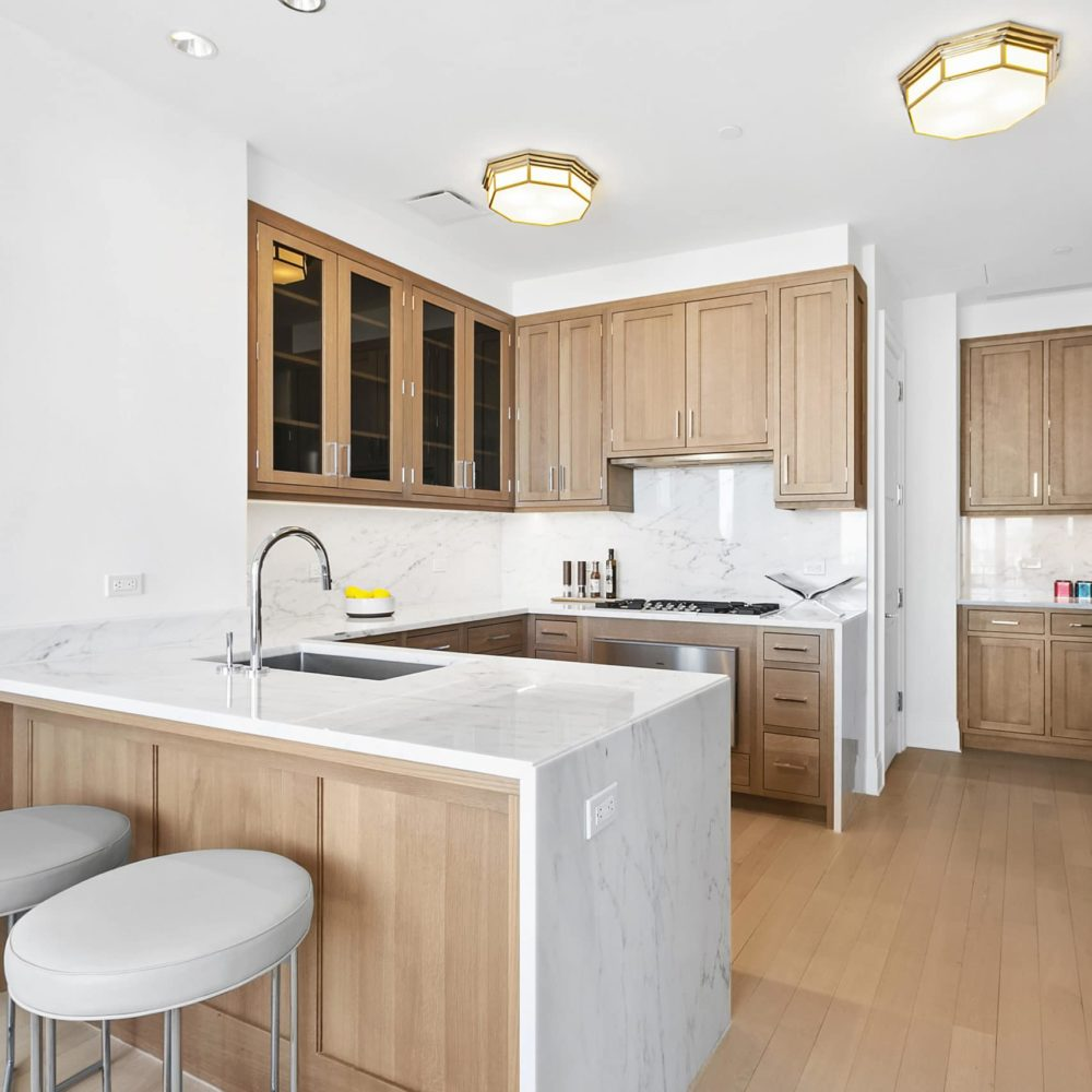 Interior view of kitchen inside 30 Park Place condominiums in NYC. Includes wood floor, white walls and white countertops.
