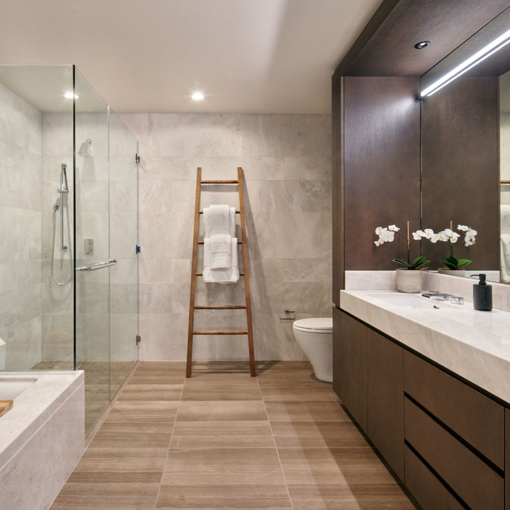Master bathroom at The Avery condos in San Francisco. White marble double vanity with mirror, a soaking tub and full shower.