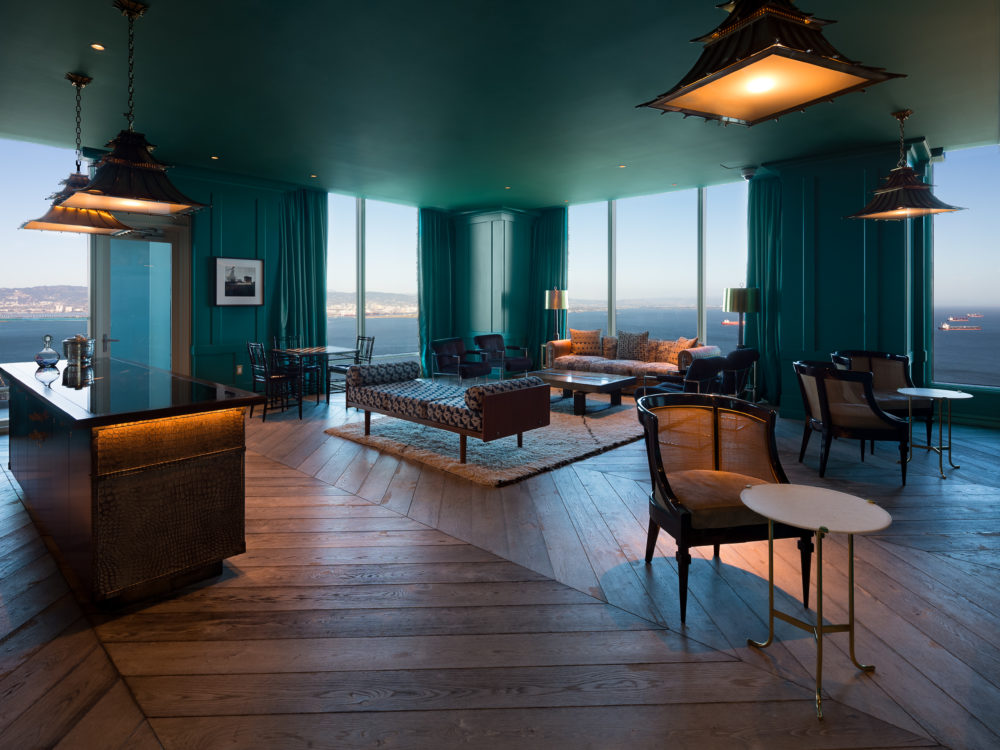 Interior view of 181 Fremont residence speakeasy with window view of San Francisco. Includes green ceilings and furniture.
