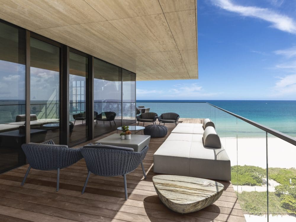 Exterior view of Arte Surfside residence balcony with oceanfront view. Has wood deck, lounging chairs and wood ceiling.