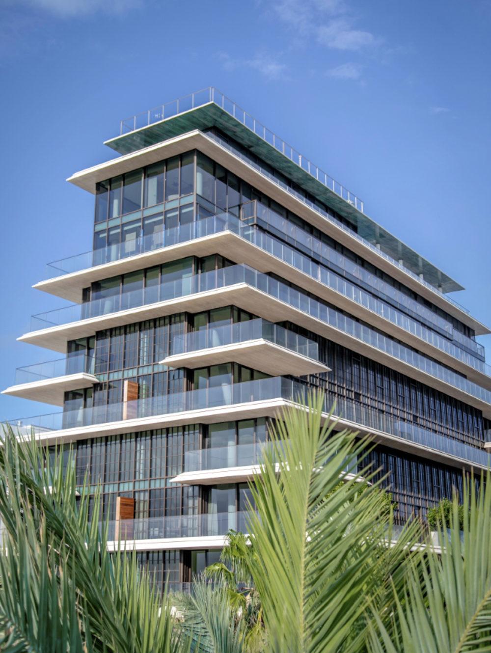 Exterior ground view of Arte Surfside condominiums. Has oceanfront view, palm trees and full architectural details.