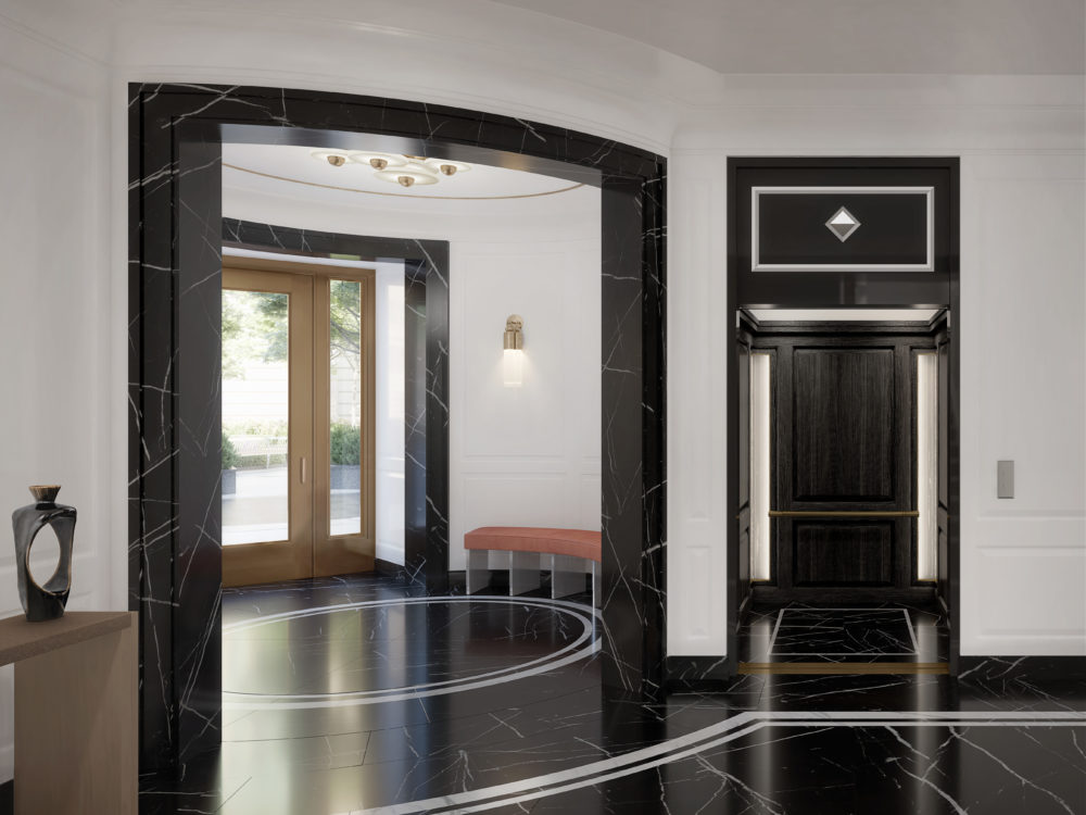 Interior lobby at The Belnord in New York. View of front doors and elevator with black marble floors and white walls.