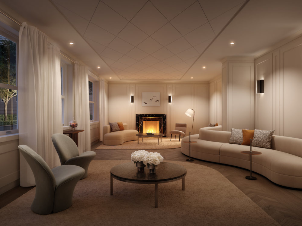 Residents lounge at The Belnord apartments in NYC with multiple seating areas, natural light, and fireplace on the back wall.