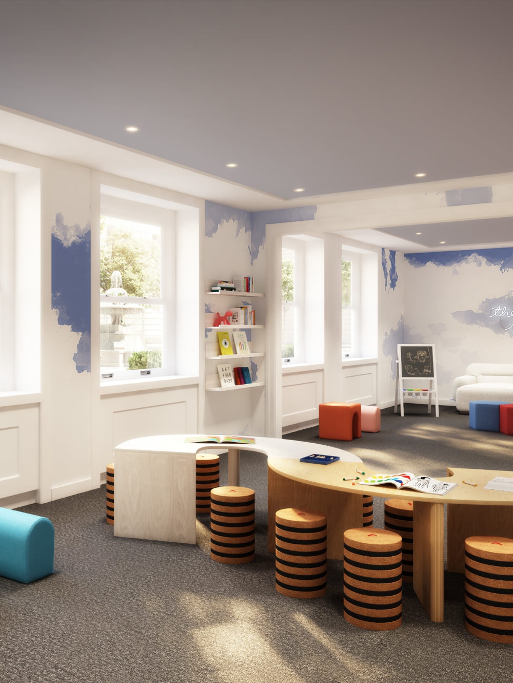 Kids lounge and playroom at The Belnord in New York. White walls with blue clouds, arts and crafts table, and play area.