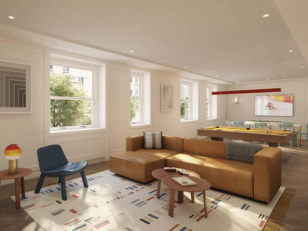A teen lounge at The Belnord luxury apartments in NYC. Open room with a couch, pool table, and game table with natural light.