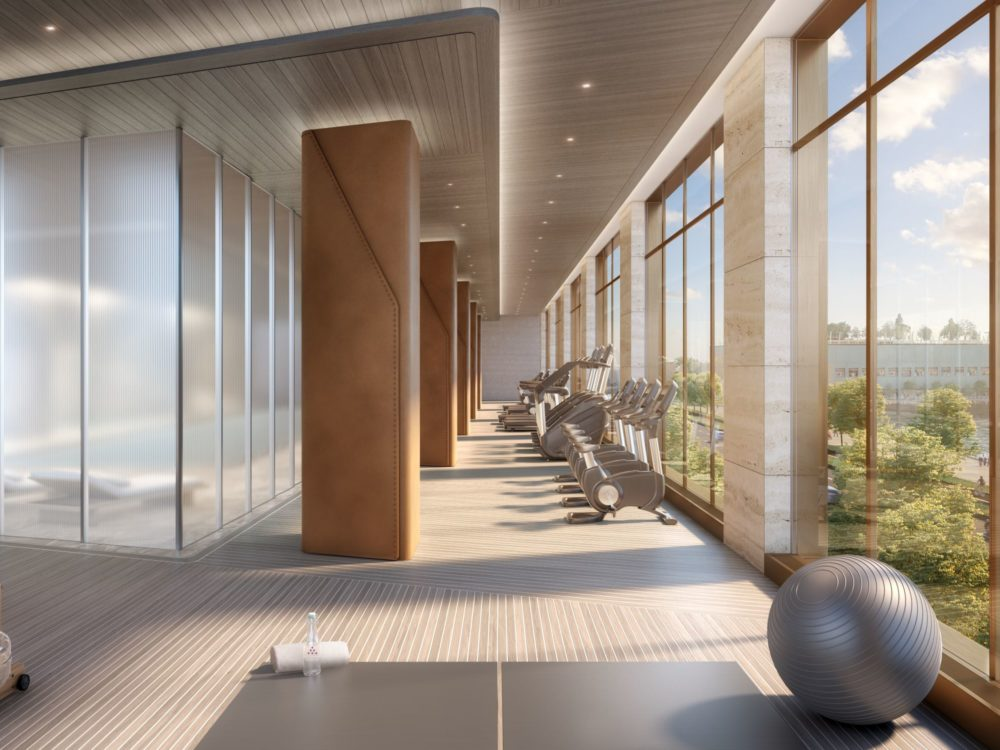 Fitness center at The Xi condos in New York. Long room with glass walls featuring treadmills, ellipticals and row machines.