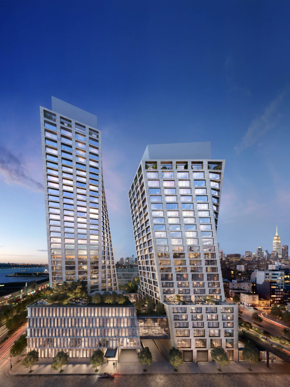 Exterior view of The Xi luxury condos in New York. Two towers of glass and travertine with the city in the distance at dusk.