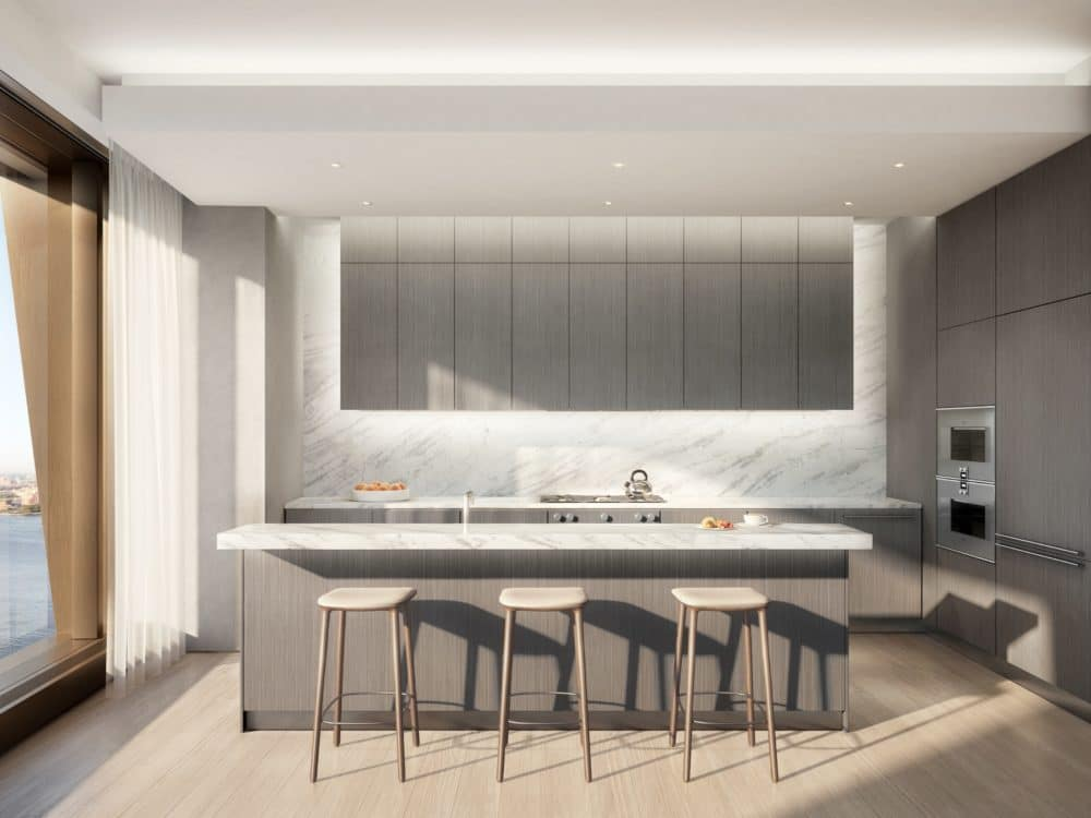 A kitchen at The Xi condos in New York. Gray walls and cabinets, a small island countertop and floor-to-ceiling windows.