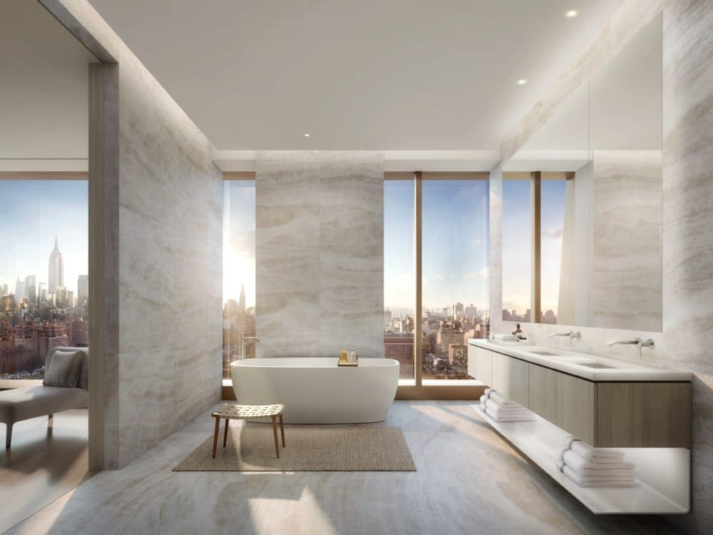 Master bathroom in The Xi luxury condos. Light gray walls, double vanity, and soaking tub with large windows with city views.