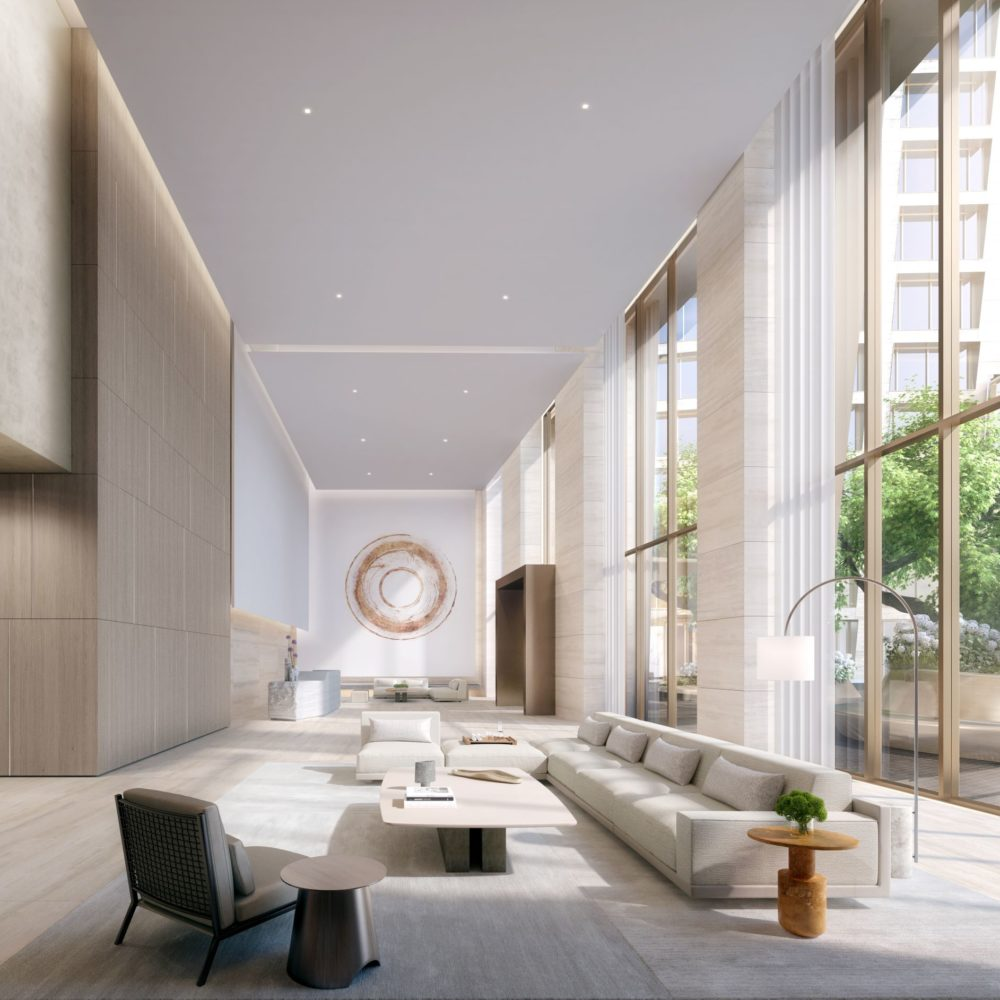 Interior view of the west tower lobby at The Xi condos in New York. Light colored walls and furniture with large windows.
