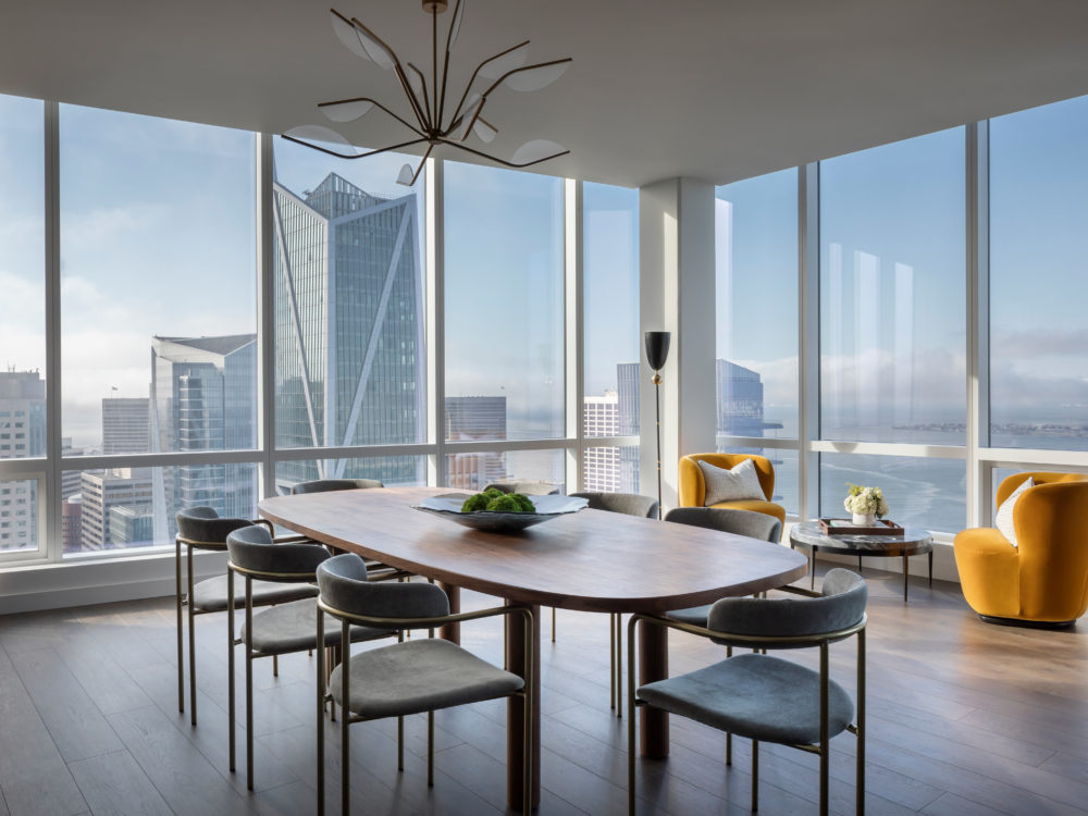 Corner dining room with floor-to-ceiling windows with Bay area skyline views at The Avery luxury condos in San Francisco.