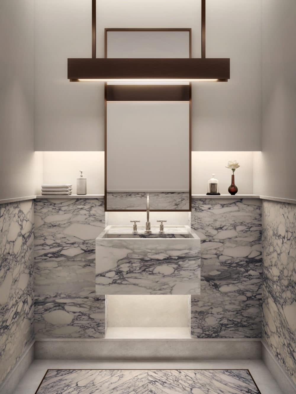 Close up of a powder room in The Xi condos in NYC. Stone sink and floor, hanging lights of the sink and mirror on white wall.