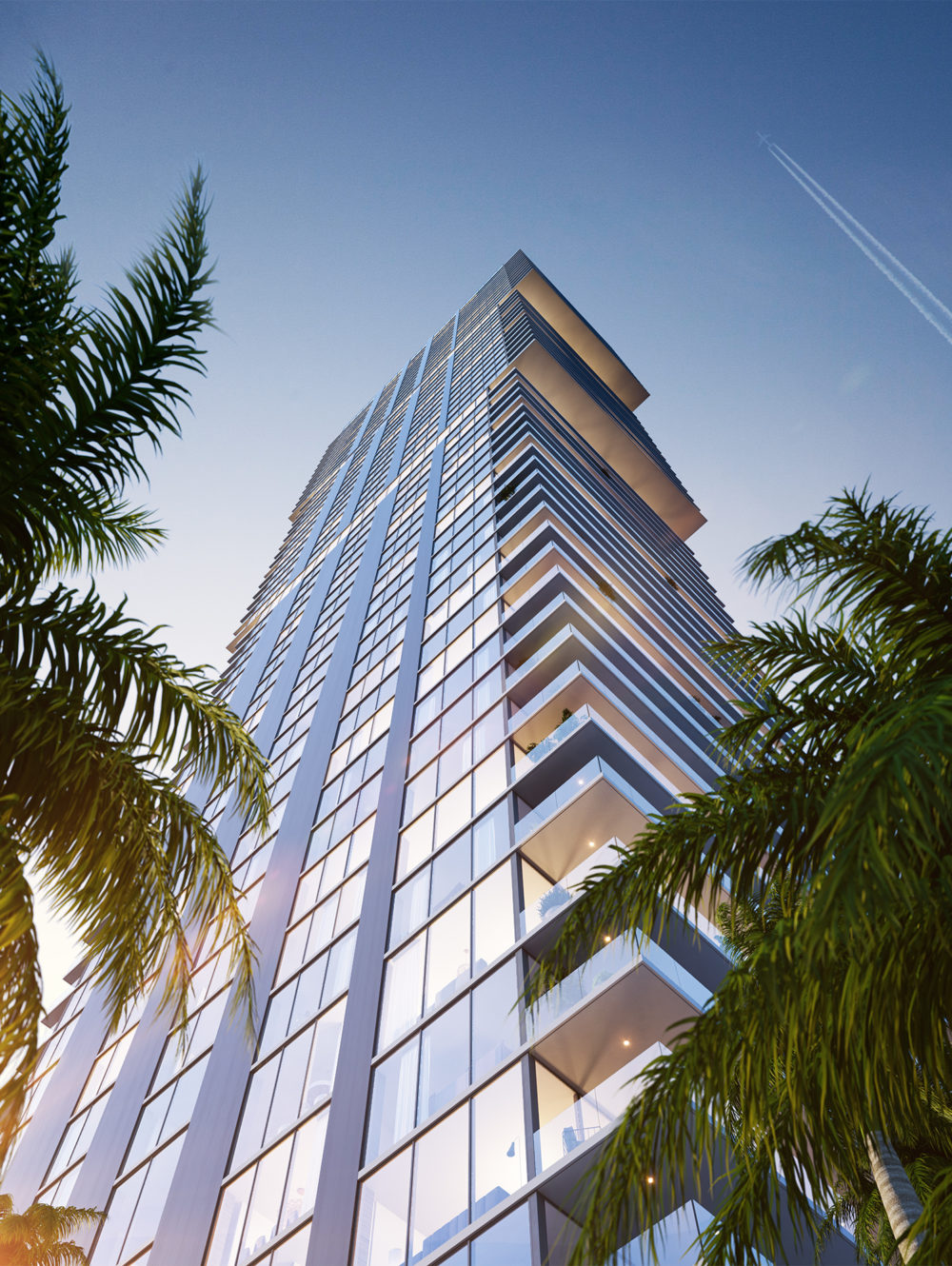 Exterior ground view of Elysee condominiums with view of Biscayne Bay. Includes palm tree and the sun illuminating the side.