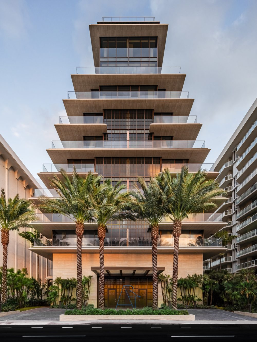 Exterior view of Arte Surfside condominiums entrance. Has oceanfront view, palm trees and full architectural details.