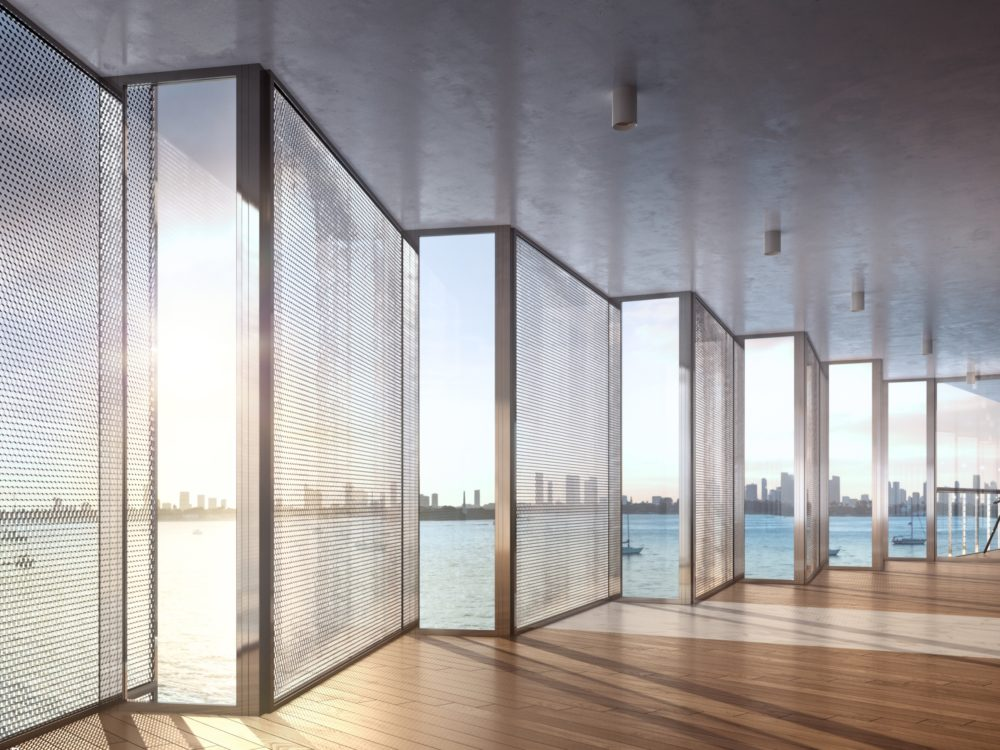 Interior at Monad Terrace condos in Miami. Open space with wood floors & honeycomb pattern glass walls with views of the bay.