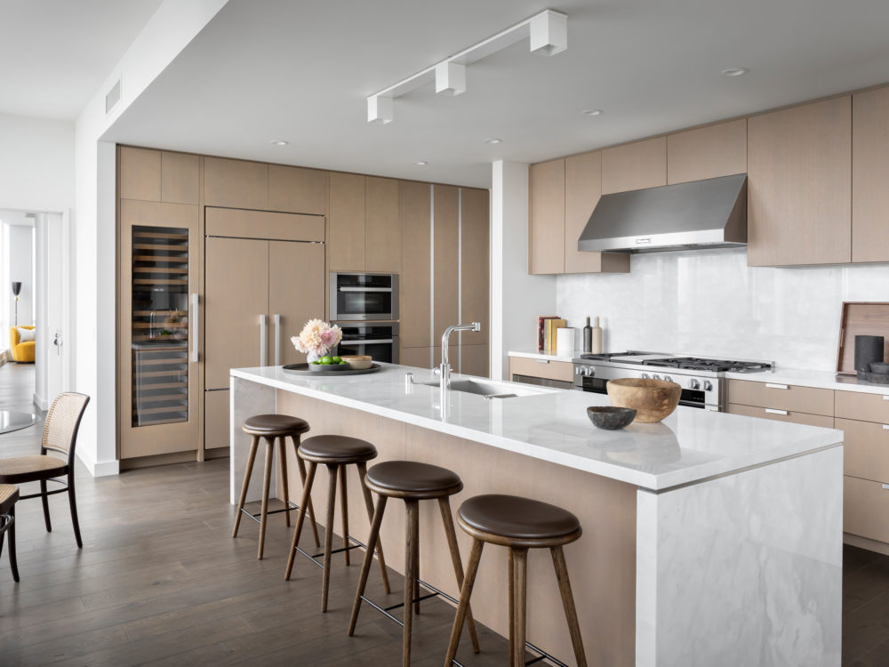 Kitchen at The Avery condos in SF. Light brown cabinets, white marble countertops, and an island with bar seating.