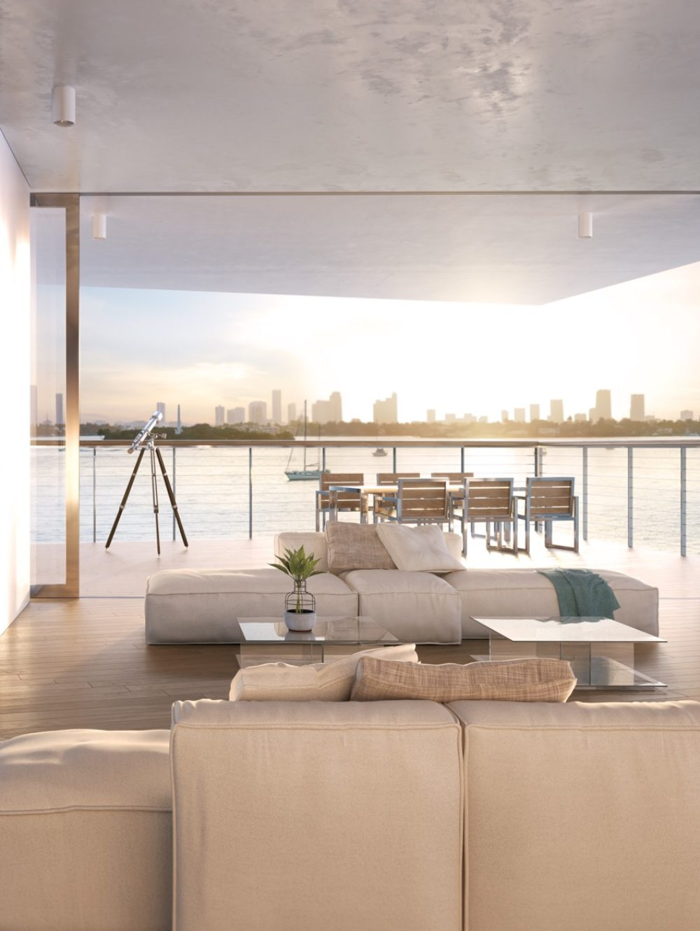 Condo living room at Monad Terrace in Miami. Couch, deck, and floor-to-ceiling windows with views of Biscayne Bay.
