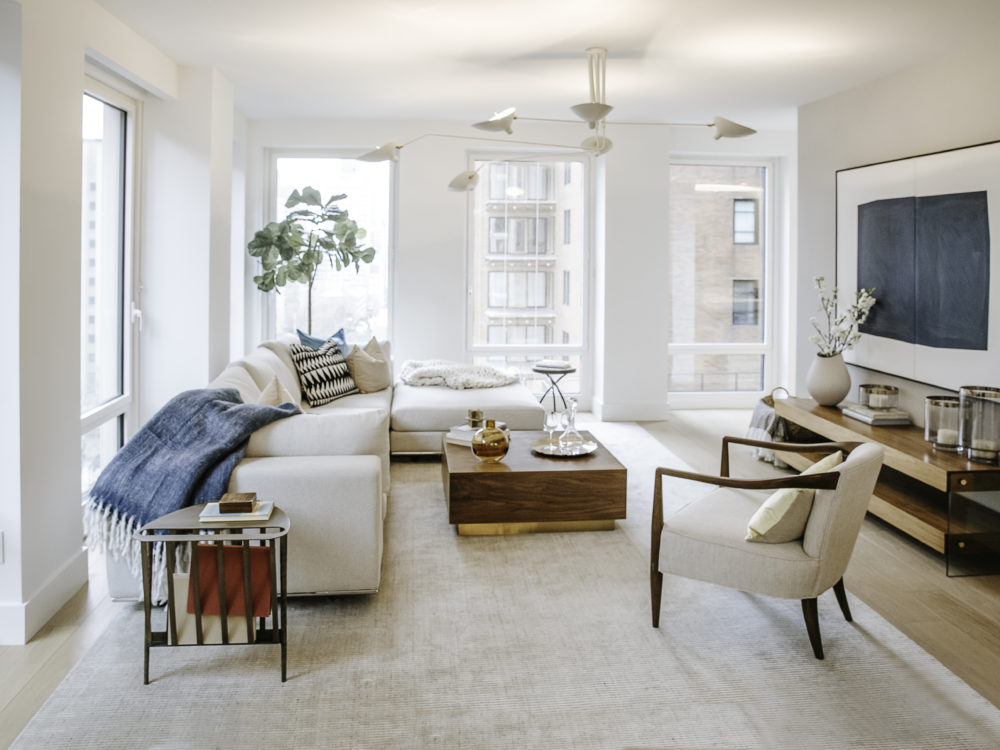 Living room at the Park Loggia condos in NYC. Open space with tall windows, oak floors, a rug, long couch and coffee table.