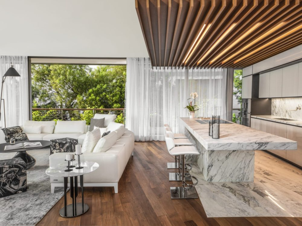 Open living space at Monad Terrace condos in Miami. Kitchen with large island, furnished living room and large windows.