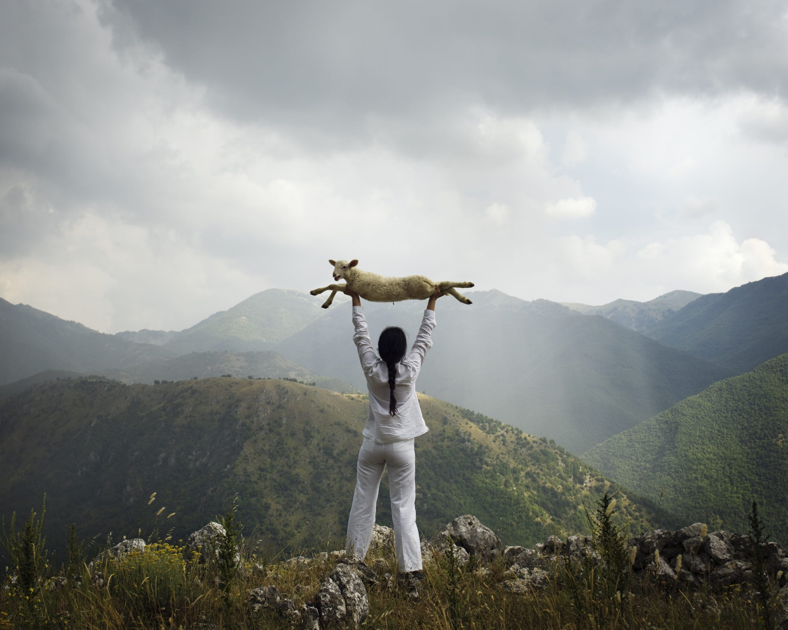 Picture of a woman holding a lamb above her head looking out at the mountains in the distance with dark clouds in the sky.