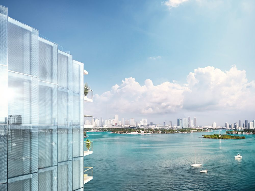 Aerial view of Biscayne Bay in Miami with exterior of Monad Terrace condos and city skyline in the distance with blue skies.