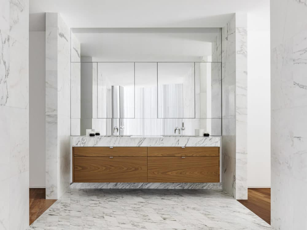 Master bathroom at Monad Terrace luxury condos in Miami. Stone walls and double vanity with full mirror and wood finishes.