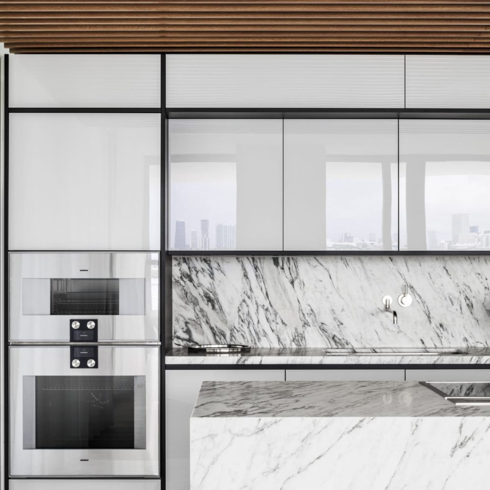Kitchen at Monad Terrace luxury condominiums in Miami. Stone island and backsplash with white cabinets and appliances.
