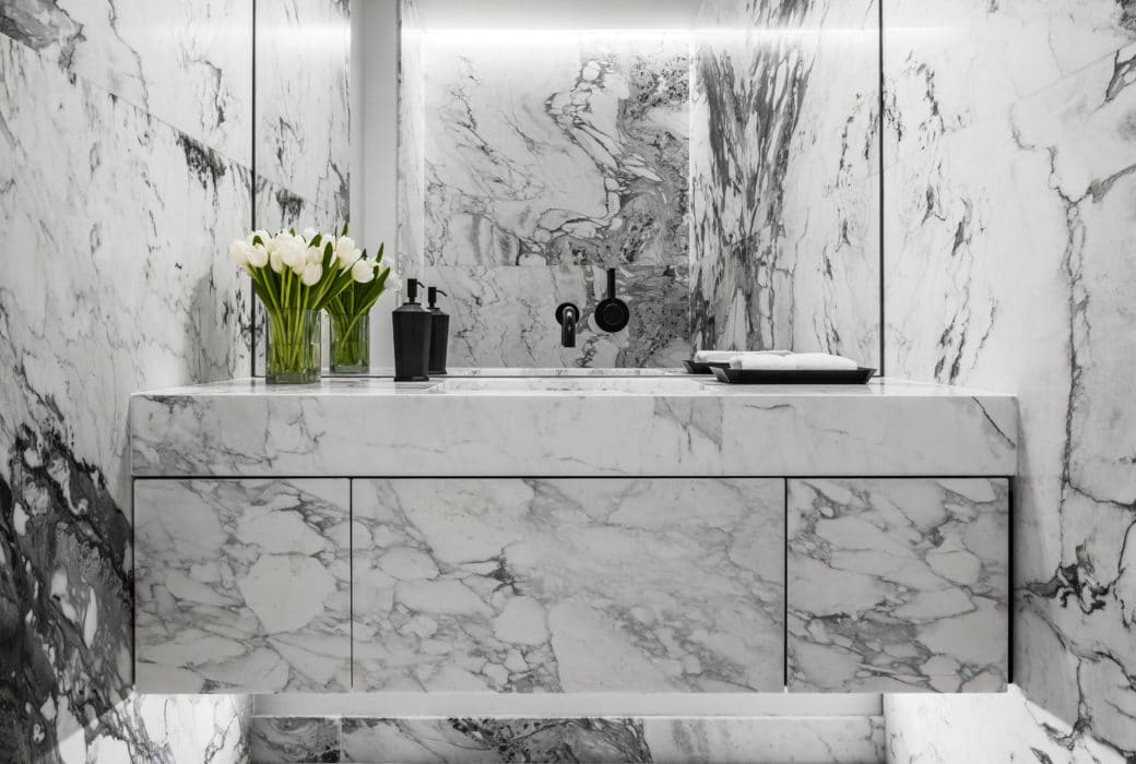 Bathroom at Monad Terrace condominiums in Miami. Veined stone make up the floor, walls, and vanity with full mirror and sink.