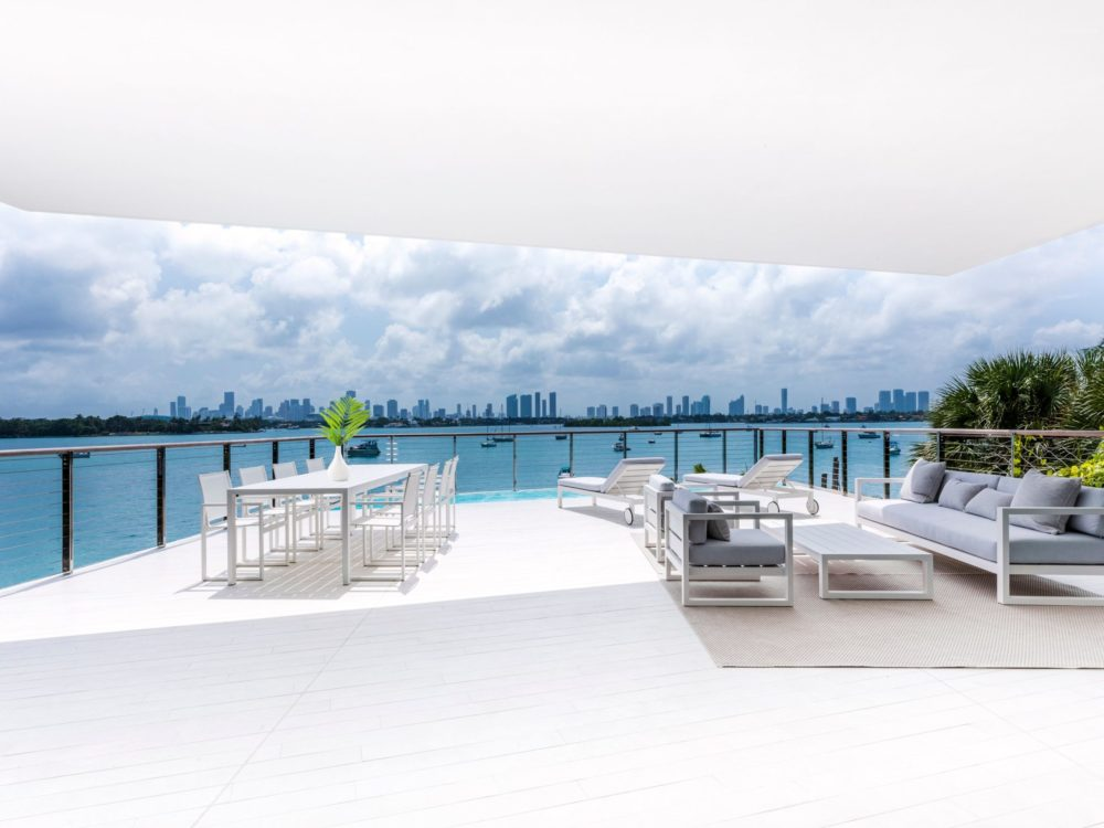 View from the terrace at Monad Terrace luxury condominiums in Miami. White floor and glass railings with seating area.