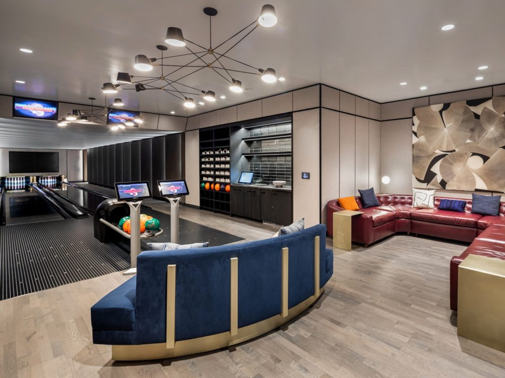 Residents bowling alley at One Manhattan luxury condominiums in NYC. Two bowling lanes, bowling ball rack and couches.