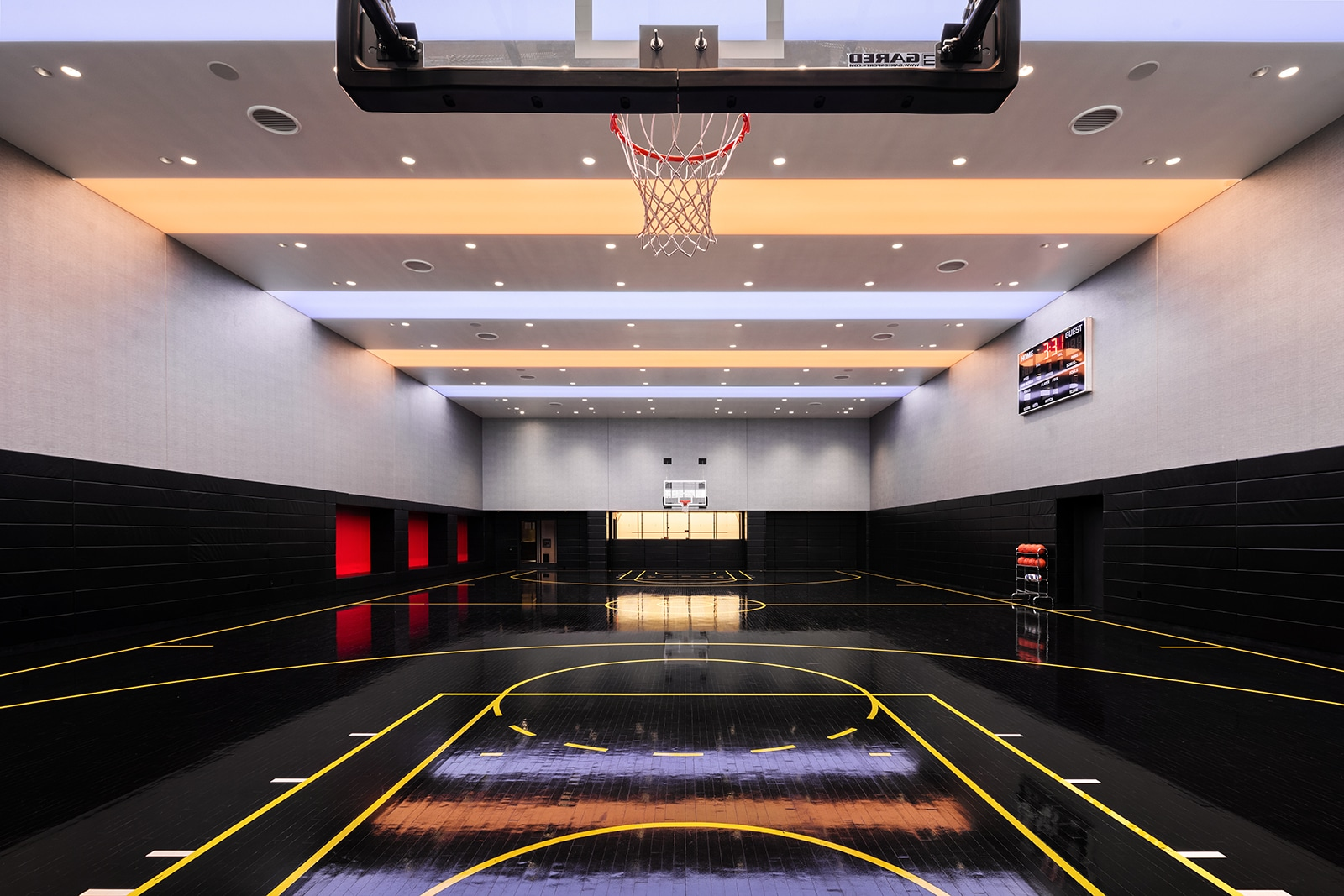 Full sized basketball court at One Manhattan Square condos in New York City. Black court with two hoops and scoreboard.