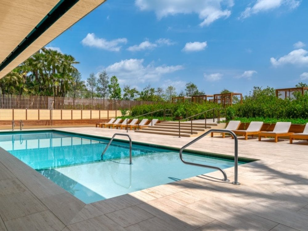 Exterior view of Arte Surfside condominiums outdoor pool with oceanfront view. Has lounge chairs and covered cabanas.
