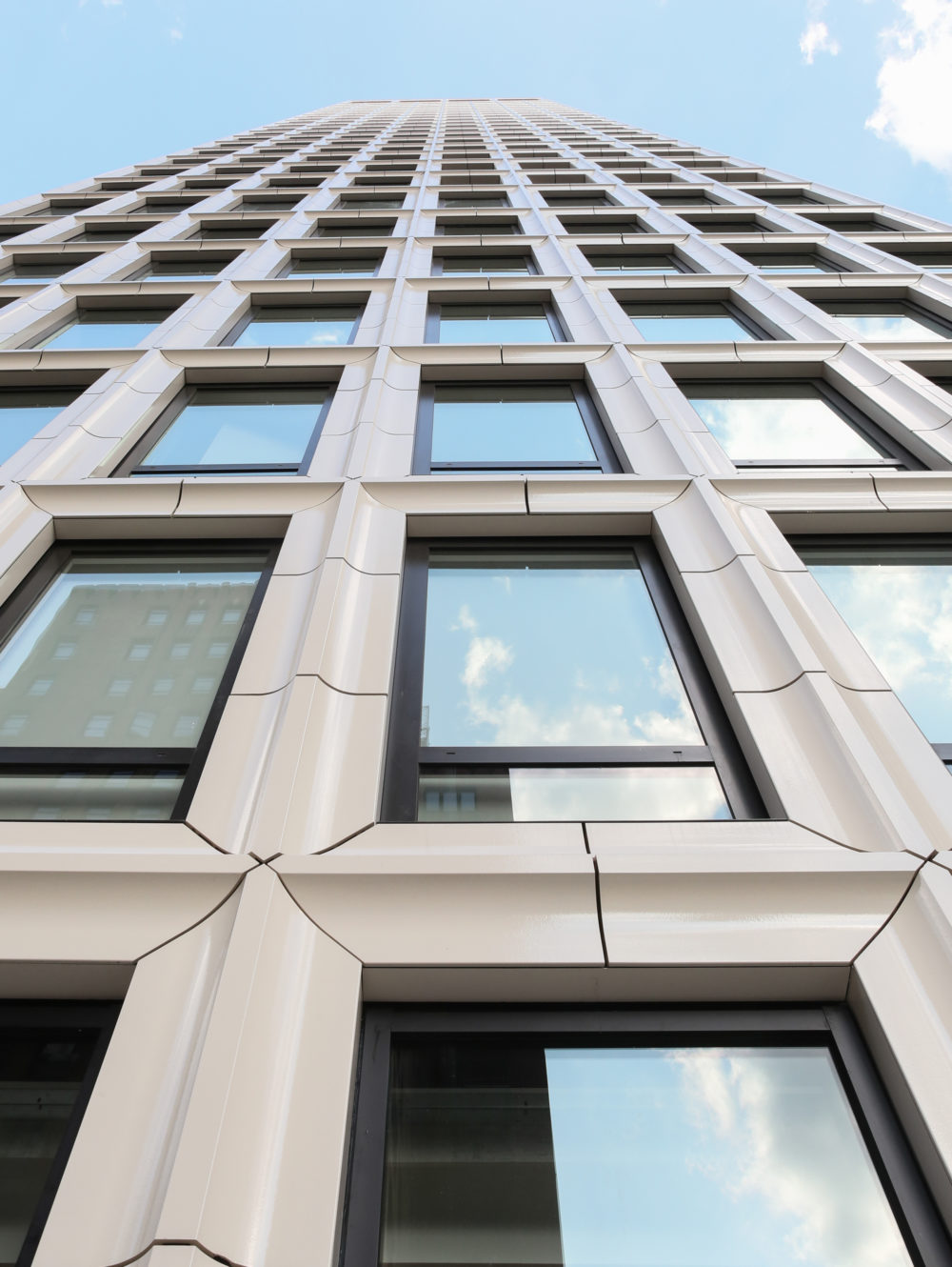 View of the Park Loggia condos exterior in New York. Looking up the side of a high rise with large windows and white stone.