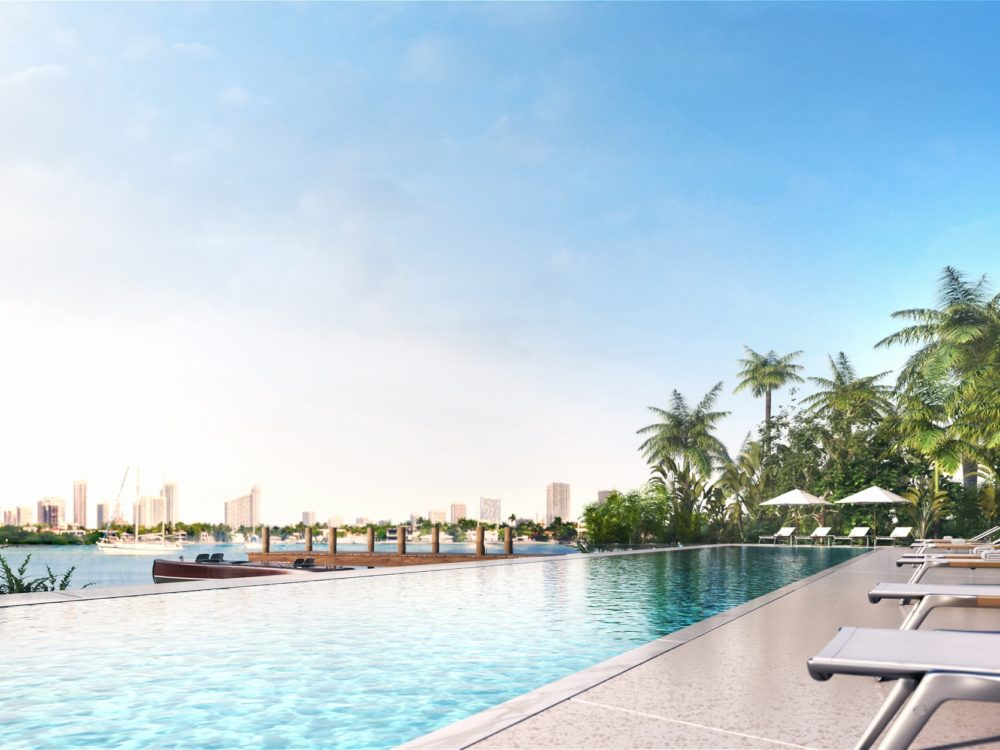 Pool at Monad Terrace luxury condominiums in Miami. Pool side with lounge chairs and palm trees overlooking Biscayne Bay.