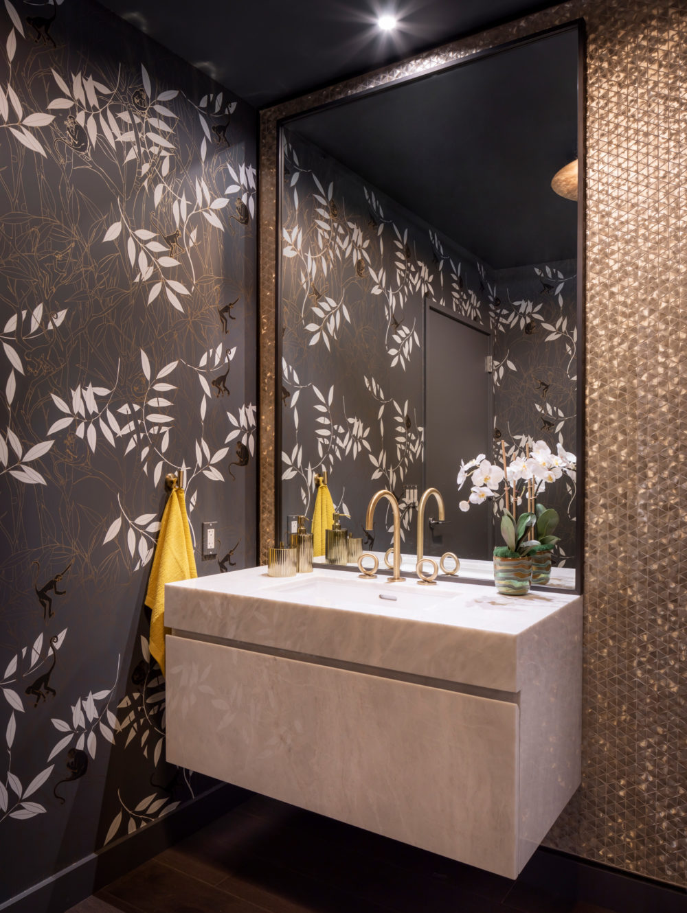 Powder room at The Avery luxury condominiums in SF. Floral wallpaper, marble vanity with gold accents and a large mirror.
