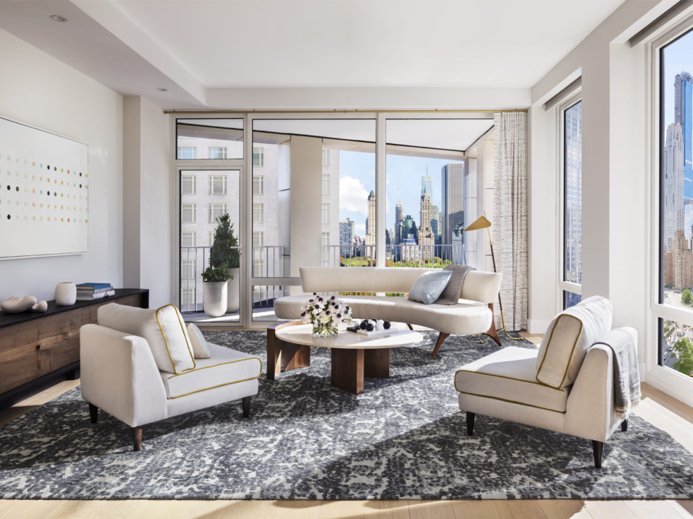 Living room at the Park Loggia in New York City. Large windows, natural light, and white oak floors with rug, couch & chairs.