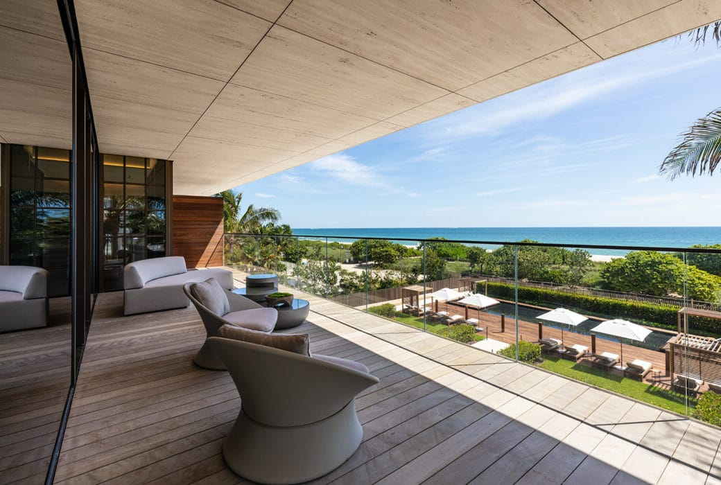 View of ocean front balcony of Biscayne Bay at Arte Surfside condominiums. Has wooden flooring and shade covering.