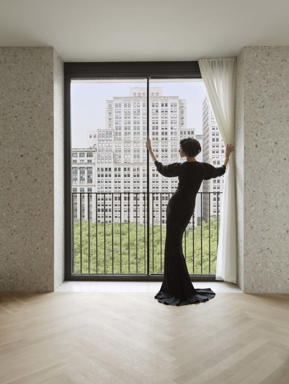 A woman in a black dress looking out floor-to-ceiling windows with a view of the park at The Bryant condos in New York.