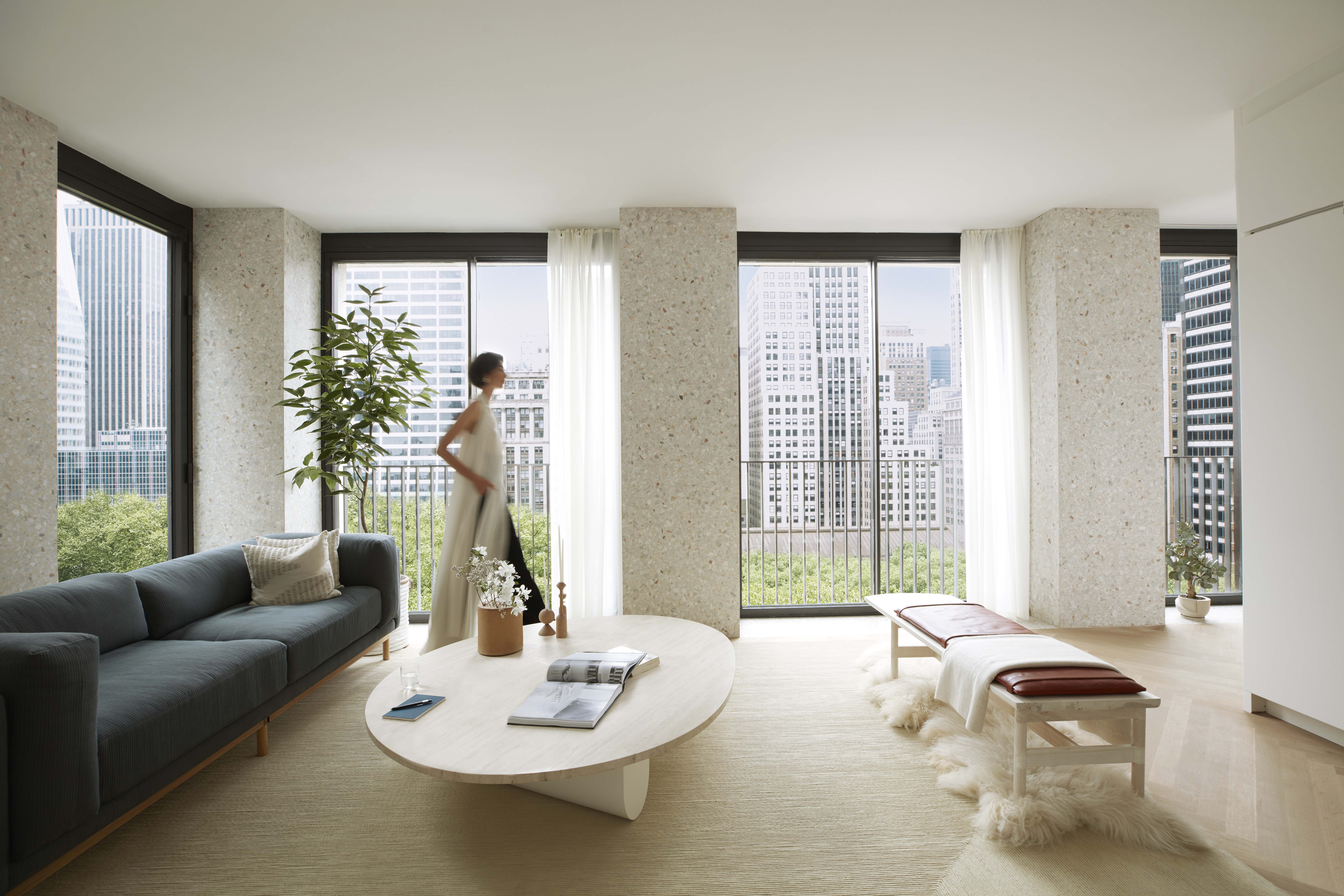 Living room at The Bryant condos in New York. Woman walking in front of the oversized windows overlooking Bryant Park.