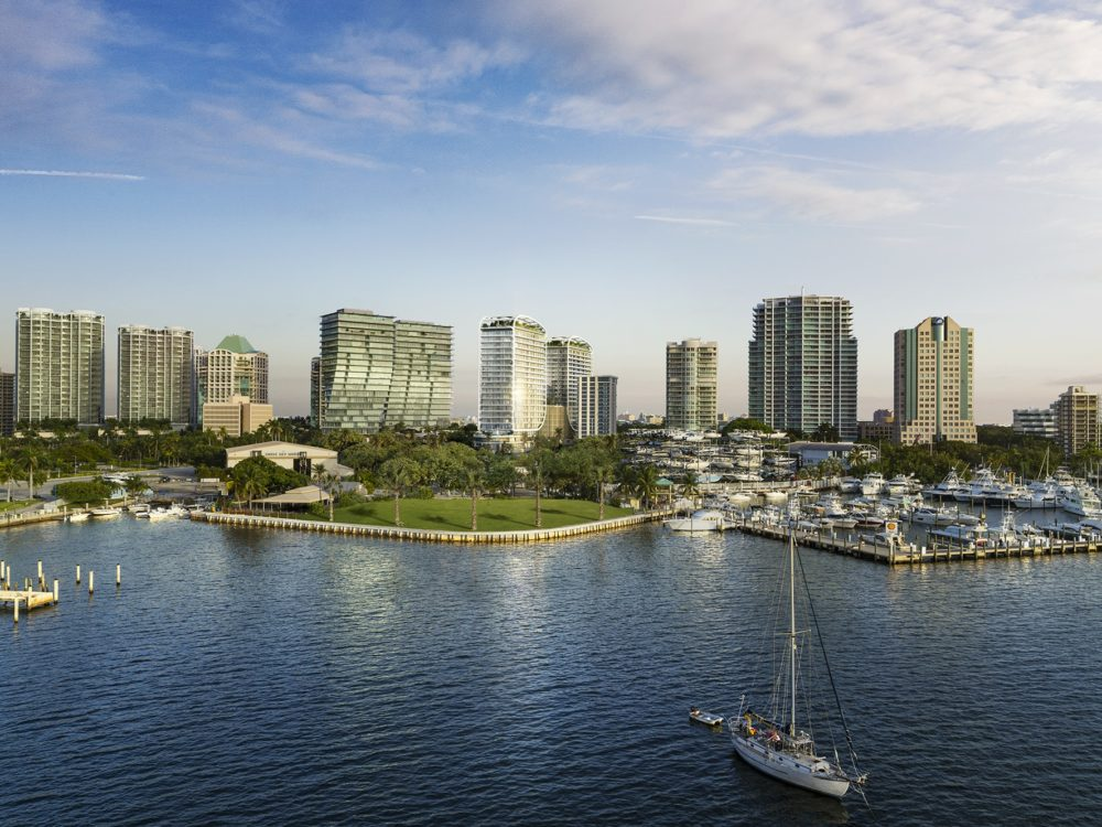 Aerial view of Biscayne Bay marina with high rises on the coastline, including Mr C. Residences in Coconut Grove, Miami.